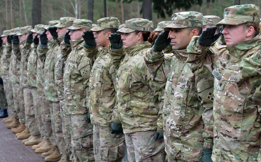 American rotational soldiers of the 4th Infantry Division salute during the national anthem at a welcoming ceremony for them in Zagan, Poland. The U.S.plans to deploy more troops to Poland, the U.S. ambassador to the country, Georgette Mosbacher, said Wednesday.