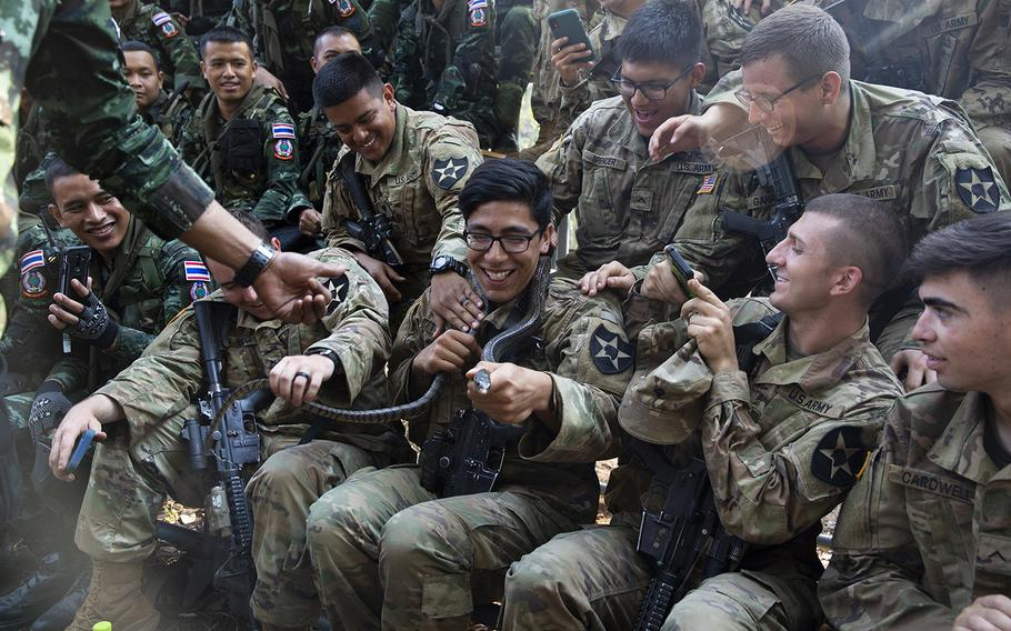 U.S. Army Spc. James S. Teaney with Bravo Company, 5th Battalion, 20th Infantry Regiment, holds a snake during exercise Cobra Gold 19 at Phitsanulok, Thailand, on Feb. 13, 2019.