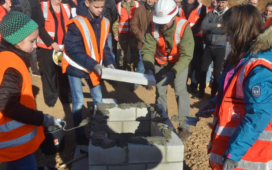 With the help of the construction workers, students from the current Wiesbaden Elementary School bury a time capsule in the foundation of the new school in Wiesbaden, Germany, on Thursday, Feb. 14, 2019.