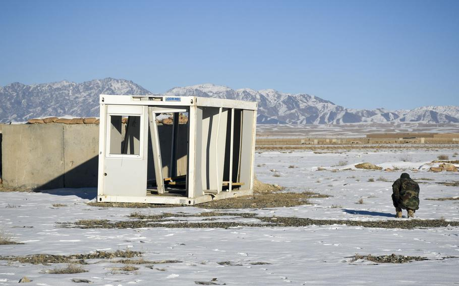 An Afghan soldier crouches near the remains of a shipping container at what was once Forward Operating Base Shank in Logar province.