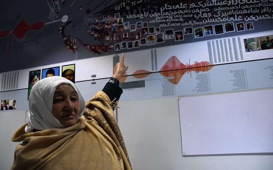 Sima Dawlatshahi on Feb. 20, 2019, points to a photo of her son who was killed in a 2016 suicide blast. The photo adorns a wall of the Center for Memory and Dialogue in Kabul, which opened in February to pay tribute to Afghan killed during the past four decades of conflict that have plagued the country.