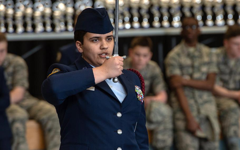 Natalie Toney salutes as she competes in the dual saber exhibition during the DODEA-Europe JROTC drill team championships at Ramstein, Germany, Saturday, March 2, 2019.