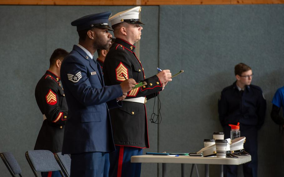 Staff Sgt. Garrett Rhodes and Gunnery Sgt. Matthew Nolan judge the rifle solo exhibition during the DODEA-Europe JROTC drill team championships at Ramstein, Germany, Saturday, March 2, 2019.