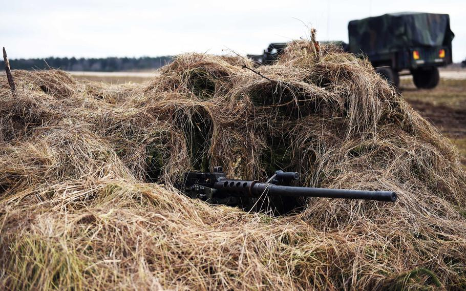 An M2 machine gun peeks out of a camouflaged position during Exercise Dynamic Front 2019, Wednesday, March 6, 2019.