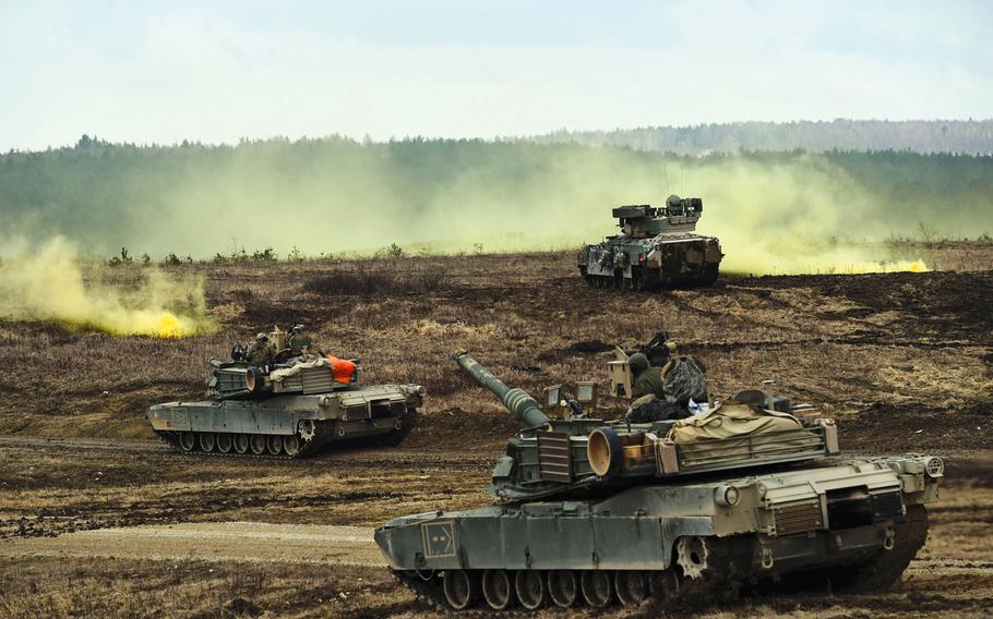 M1A2 Abrams tanks and Bradley Fighting Vehicles converge on a smoke signal during a live-fire exercise at Grafenwoehr, Germany, in March. President Trump is pushing a plan that demands allies pick up the full cost of hosting U.S. troops in their countries, plus a 50 percent premium for American protection, according to a news report.