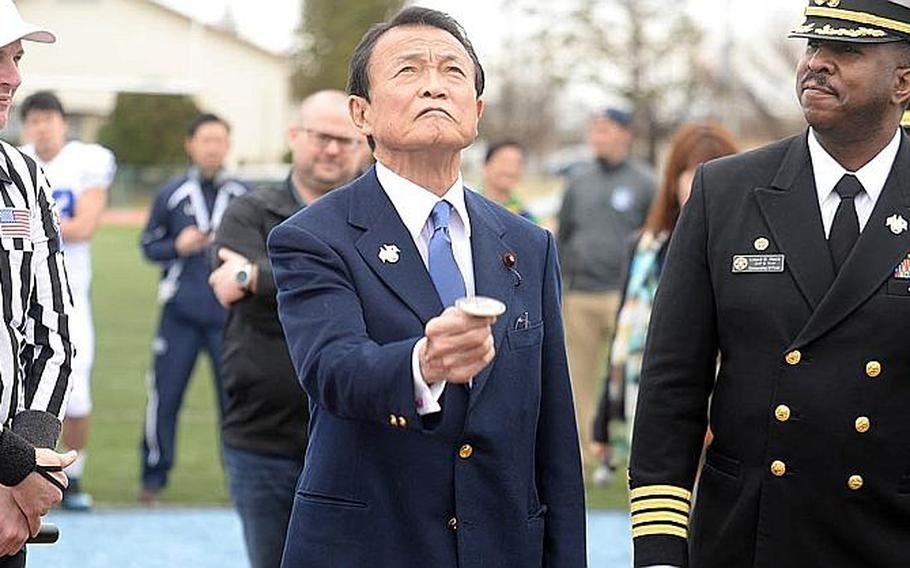 Former Japanese Prime Minister Taro Aso, flanked by game referee Matt Manning and Naval Air Facility Atsugi commander Capt. Lloyd Mack, does the pre-game coin toss at the center of the field at Reid Memorial Stadium, NAF Atsugi, Japan, March 10, 2019, before the Tomodachi Bowl friendship game.