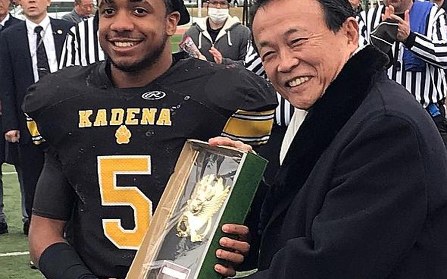 Eric McCarter of Kadena High School, Okinawa, accepts the Tomodachi Bowl MVP trophy from former Japanese Prime Minister Taro Aso at Reid Memorial Stadium, Naval Air Facility Atsugi, Japan, March 10, 2019.