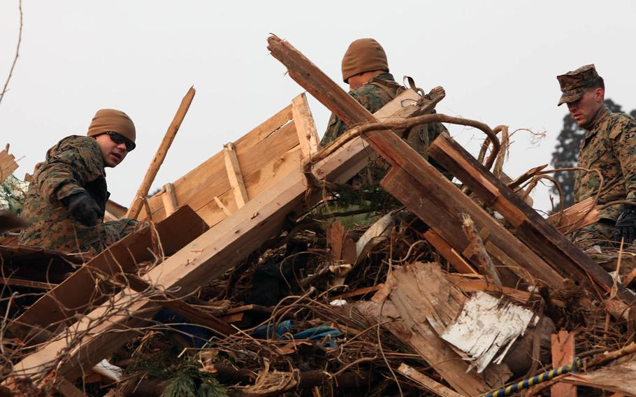U.S. Marines of the 31st Marine Expeditionary Unit pick up debris April 2, 2011, during a disaster relief mission at Uranohama Port, Oshima Island, Japan, in support of Operation Tomodachi.
