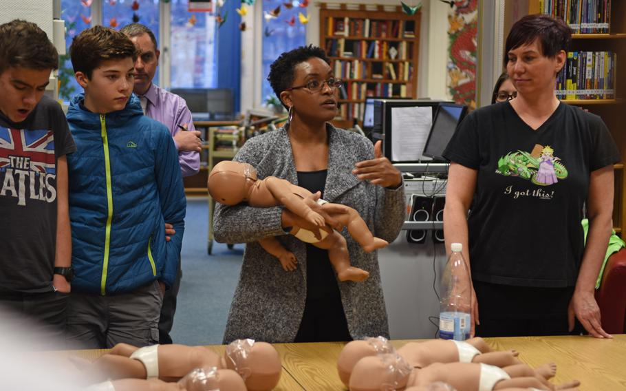 Ramstein Middle School nurse Ann Evans, center with infant mannequin, and RMS health educator Sam Jablonski, demonstrate the proper way to hold an infant during health class in the school's library on March, 14, 2019. More than 200 RMS students are expected to earn certificates of completion this year as a part of a unique middle school CPR and first aid training program in DODEA.