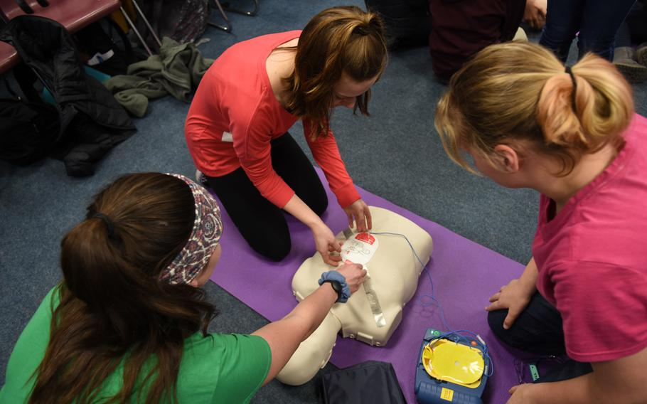 Abigail Schalla, left, Alexie Ward, and student teacher Grace Stewart, foreground, practice CPR on a first-aid mannequin with an automated external defibrillator on March 14, 2019, at Ramstein Middle School in Germany.