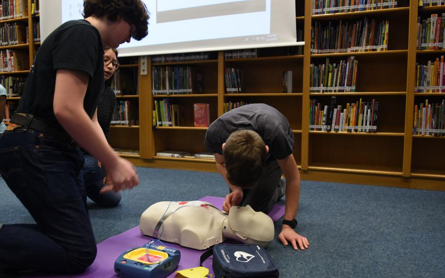 Peyton Byrns, right, and Elijah Perrow practice CPR on a first-aid mannequin on March, 14, 2019, at Ramstein Middle School in Germany.