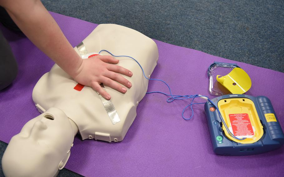 A one-handed chest compression is done on a mannequin, a technique used for CPR on a child. Eighth-graders at Ramstein Middle School in Germany are learning how to perform CPR and other emergency lifesaving procedures.