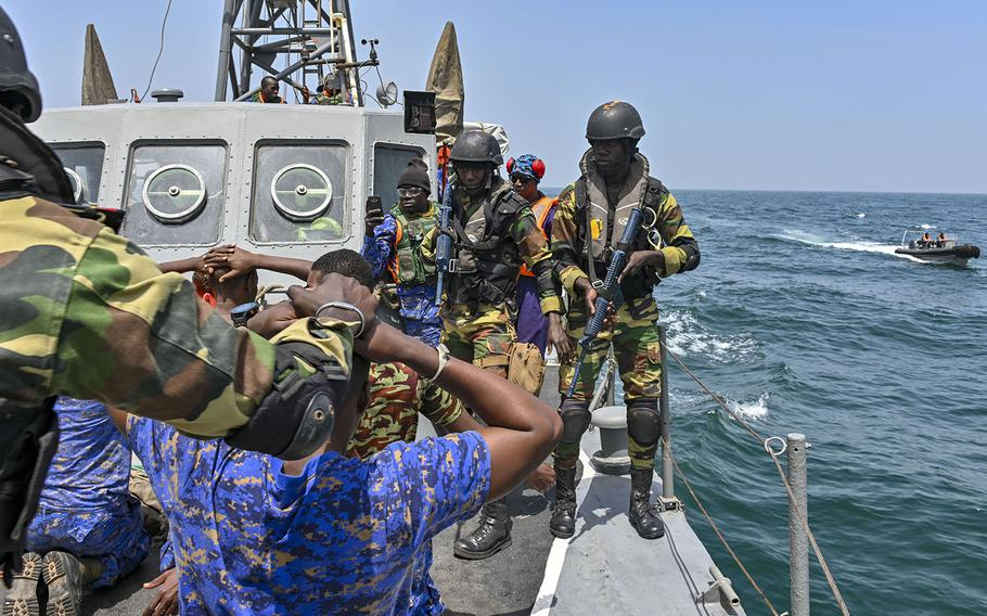 Members of the Senegalese and Gambian navies conduct a simulated search-and-seizure raid during a drug smuggling and human trafficking scenario aboard a Gambian patrol vessel on March 18, 2019 during Obangame Express. The U.S.-led exercise brought together 33 countries to practice teamwork in combating seagoing crimes in West African waters.