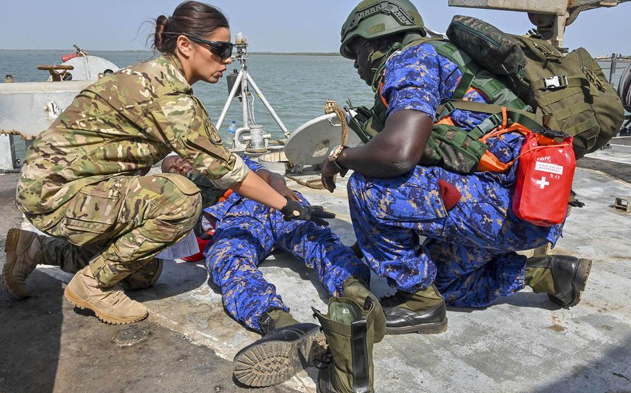 Coast Guard Petty Officer 3rd Class Alyssa Perry works with a member of the Gambian navy to treat a simulated wound during a drug smuggling and human trafficking scenario on March 18, 2019, near Gambia as part of Obangame Express. The exercise seeks to improve teamwork between West African countries to combat seaborne crimes.