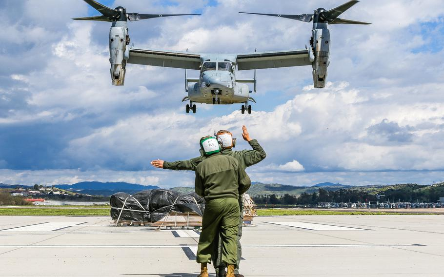 U.S. Marine Corps Sgt. Nicholas Attikai, front, 3rd Marine Aircraft Wing, directs an MV-22 Osprey while being stabilized by Sgt. Carlos Rodriguez, rear, during a hung gear malfunction drill at Marine Corps Air Station Camp Pendleton, Calif., March 12, 2019. The purpose of the drill was to ensure that in the event of a landing gear malfunction the pilot, air crew and ground crew would be trained to conduct an emergency landing.
