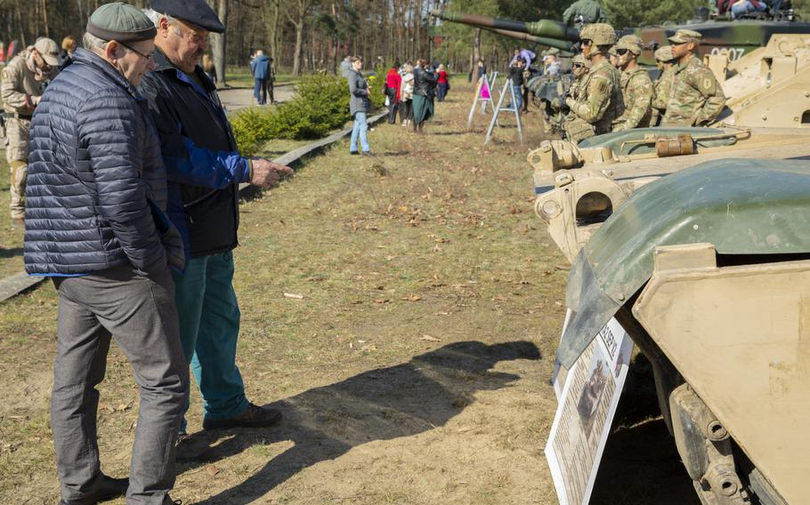 Polish locals read the information placard for an M1 Abrams tank during a commemoration event the 75th anniversary of the Great Escape from the Stalag Luft III POW camp on March 23-24, 2019.