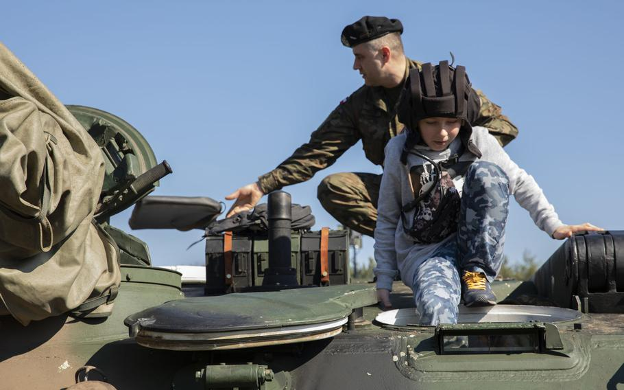 A Polish boy climbs inside of a Polish Army tank during a commemoration event for the 75th anniversary of the Great Escape from the Stalag Luft III POW camp on March 23-24, 2019.
