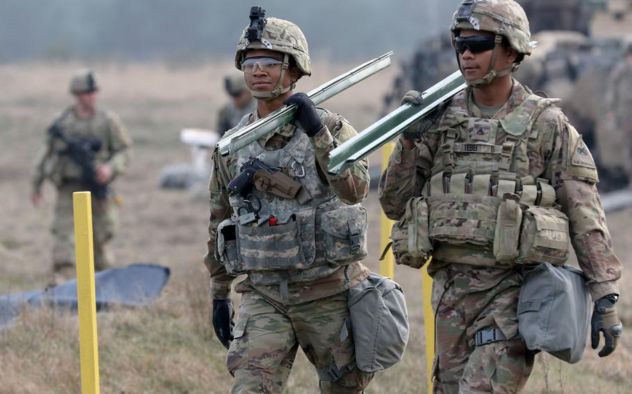 Soldiers with 2nd Armored Brigade Combat Team, 1st Armored Division out of Fort Bliss, Texas, carry stakes to mark off a sleeping area in the Drawsko Pomorskie Training Area, Poland, on March 23, 2019.