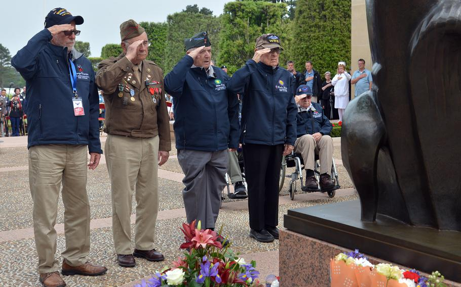A group of World War II veterans salutes after laying a wreath at the foot of the ''Spirit of American Youth Rising from the Waves'' statue at Normandy American Cemetery at Colleville-sur-Mer, in June 2018.