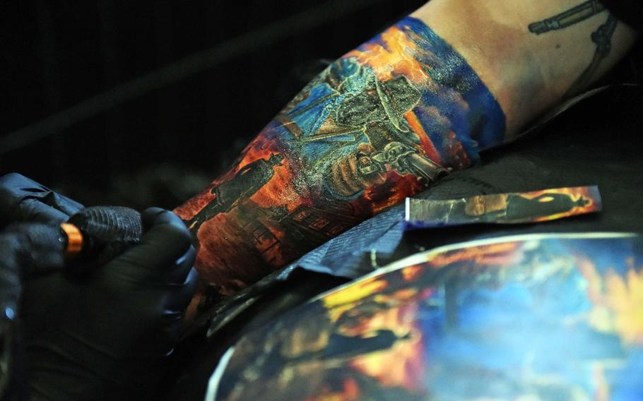 A cowboy-themed tattoo sleeve being worked on at the Grafenwoehr Tattoo Expo, in Grafenwoehr, Germany, Sunday, April 8, 2019.