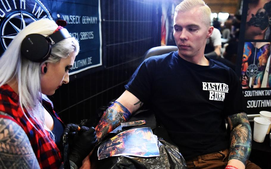 """Lisa South, a tattoo artist, works on Pvt. Rodawald Gage's """"cowboys and Indians"""" themed tattoos at the Grafenwoehr Tattoo Expo, in Grafenwoehr, Germany, Sunday, April 8, 2019. Gage is an infantryman with the Army's 2nd Cavalry Regiment."""