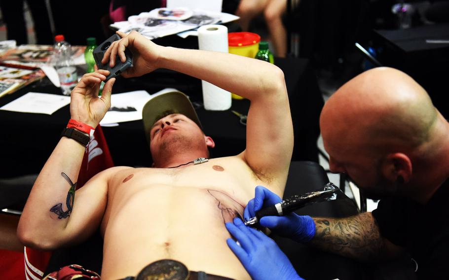 Spc. Troy Meyer, a mechanic with the 64th Military Police Company, plays on his phone to distract himself as he gets a mountain scene tattooed on his ribs at the Grafenwoehr Tattoo Expo, in Grafenwoehr, Germany, Sunday, April 8, 2019.