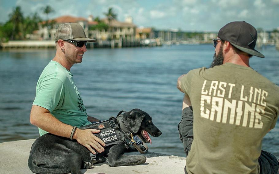 Greg Trost, left, is pictured here in Florida with his service dog Carmie and her trainer in an undated photo. Trost received Carmie through the charity Rebuilding Warriors in August 2018 to help him deal with the symptoms of a traumatic brain injury that resulted from a roadside bomb blast in Iraq in 2004. He and other Marines are raising money to donate a service dog to another Marine in need.
