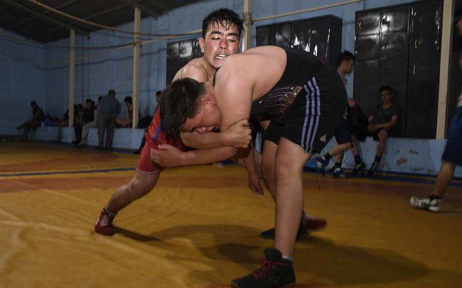 Two young wrestlers, Salman, 24, in red, and Najibullah, 19, in blue, grapple during a night session at the Maiwand Wrestling Club in Kabul on April 7, 2019.