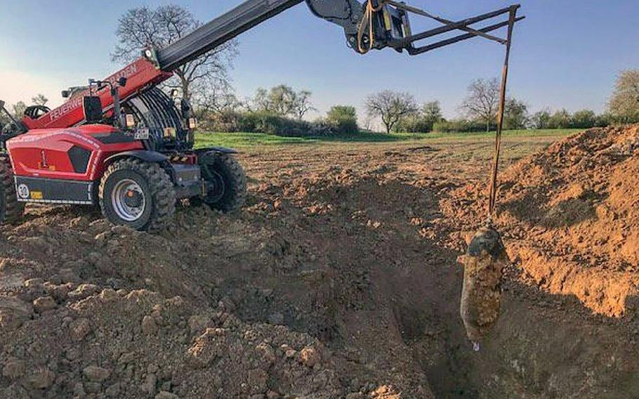 Workers remove a World War II-era bomb discovered in the vicinity of military facilities in Wiesbaden, Germany, after it was defused Thursday evening.