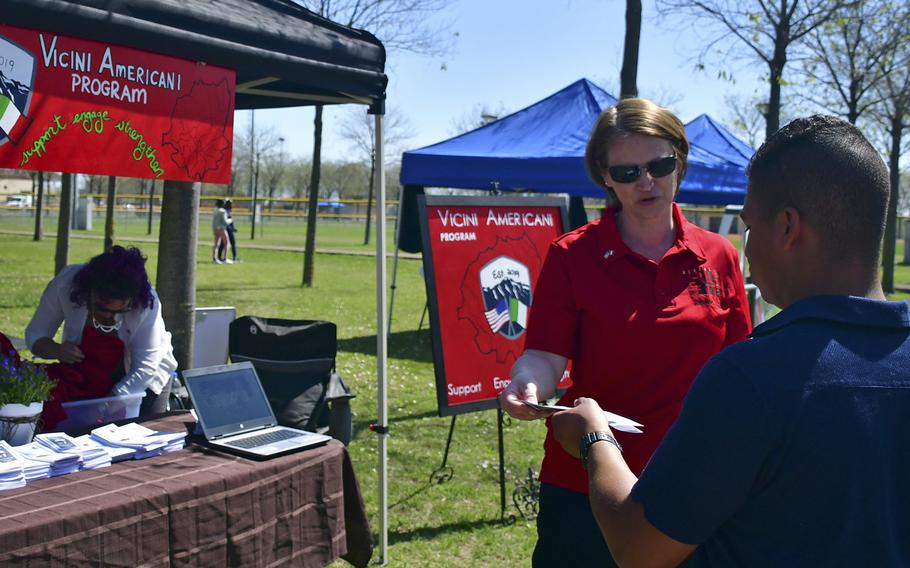 Master Sgt. Corina Cruceanu, one of the Vicini Americani program managers, speaks with a potential volunteer during the Spring Into Spring Festival at Aviano Air Base's Freedom Park, April 19, 2019. Some of the program?s goals are to foster friendship and cooperation among Americans and Italians living as neighbors in the surrounding communities.