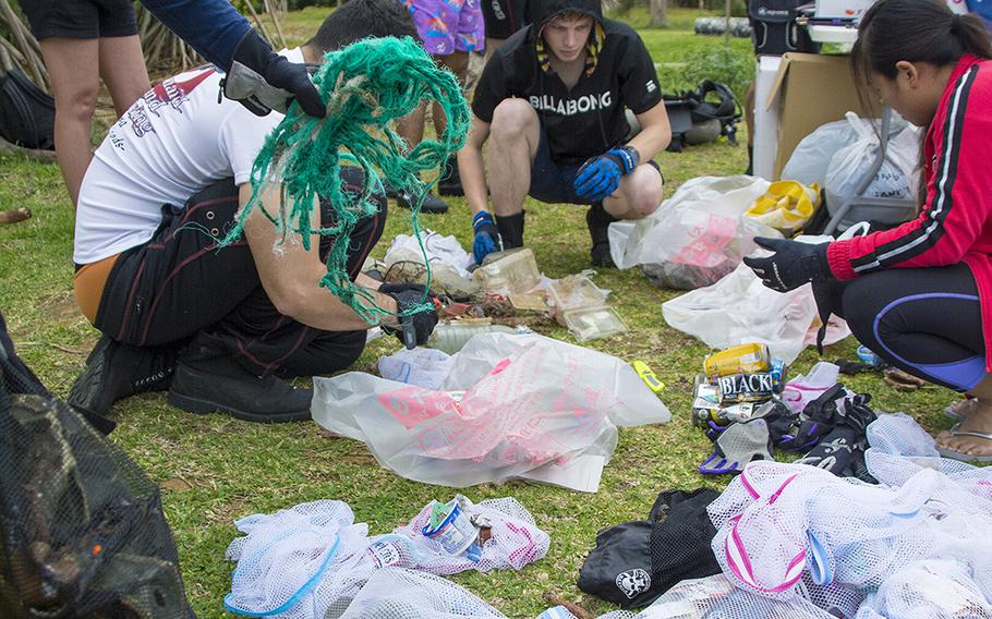 Volunteers sort garbage collected from the ocean during a cleanup event hosted by Mermaid Island Diving and Project Aware in Chatan, Okinawa, Saturday, April 20, 2019.