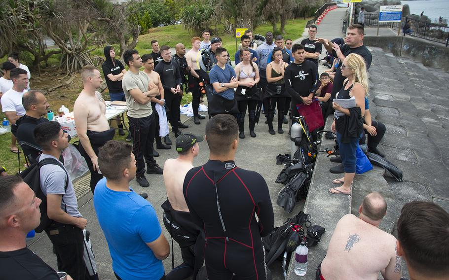 Gunnery Sgt. Scott Dahn and his wife, April Dahn, owners of Mermaid Island Diving, speak to volunteer scuba divers and snorkelers during an ocean cleanup event in Chatan, Okinawa, Saturday, April 20, 2019.