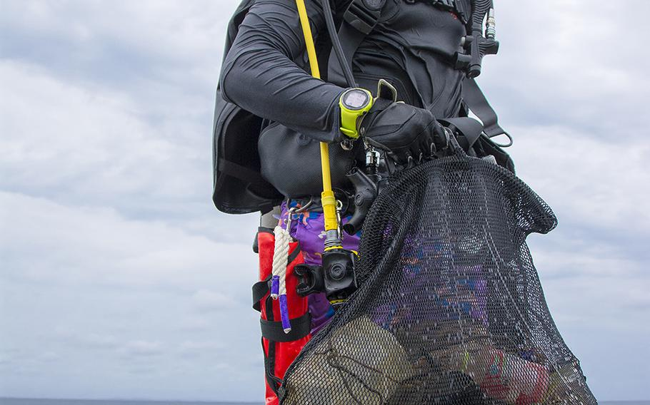 A volunteer scuba diver comes to shore with garbage he collected from the ocean during a cleanup event in Chatan, Okinawa, Saturday, April 20, 2019.