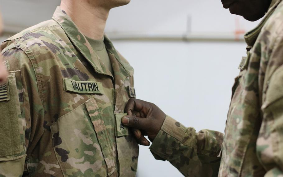 Sgt. 1st Class Colin Anderson attaches sergeant rank on Jon Vautrin's uniform during a promotion ceremony at Camp Arifjan, Kuwait, April 1, 2019. The Army is revamping its promotion board processes to focus promotions on merit, not time served. It is the first major overhaul of the system since 1969, the Army said.