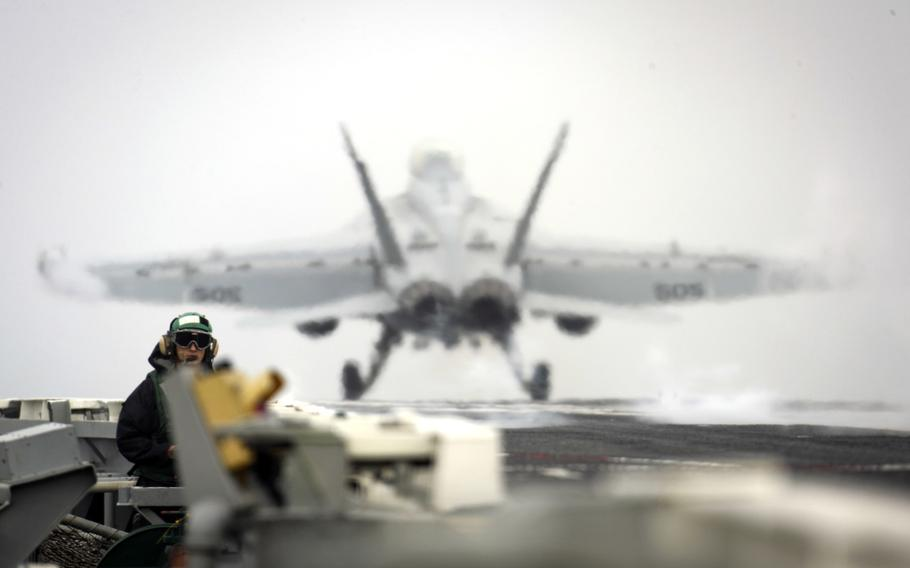 Seaman Kenneth Mathison, an airman, stands watch as an EA-18G Growler from the Electronic Attack Squadron 140 launches from the flight deck of the aircraft carrier USS Abraham Lincoln in the Mediterranean Sea, April 21, 2019.