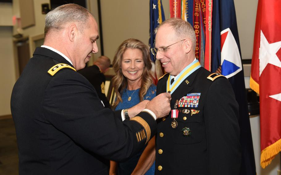 Maj. Gen. Allan Elliott receives honors at his March 28, 2019, retirement from Army Materiel Command Gen. Gus Perna, who officiated at the ceremony. The Army may need to pay a larger midcareer incentive to retain officers under the newly introduced blended retirement system, according to a Rand Corp. report.
