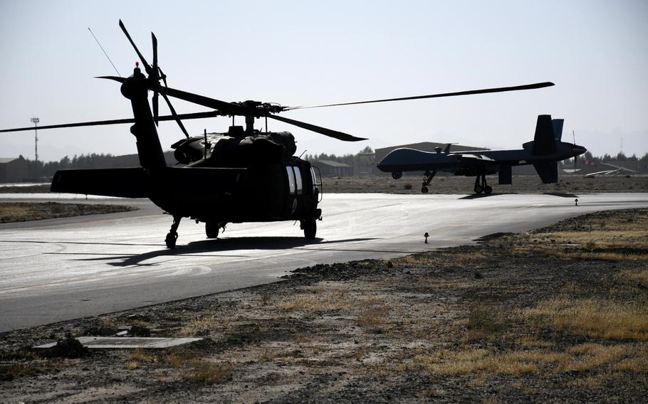 An Afghan air force UH-60 Black Hawk helicopter and an MQ-9 Reaper drone used during counterterrorism operations by the U.S. military in Afghanistan, cross paths at Kandahar Air Field on Nov. 5, 2017.