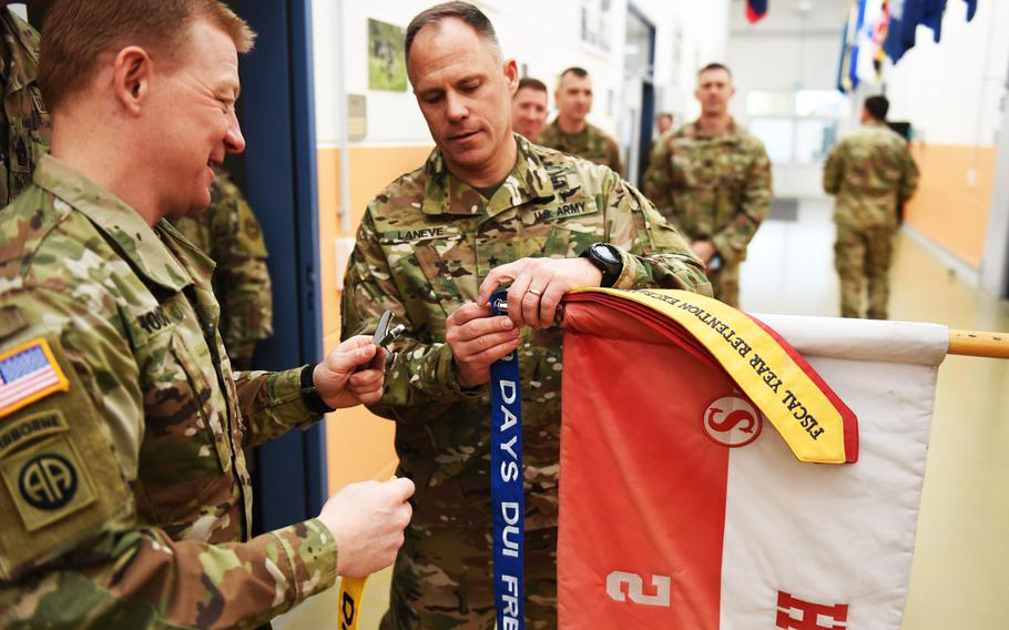 """Col. Thomas Hough, the 2nd Cavalry Regiment commander, left, and Brig. Gen. Christopher LaNeve, the 7th Army Training Command commanding general, fix """"No DUI Streamers"""" to a squadron's guidon during a ceremony, Friday, April 19, 2019."""