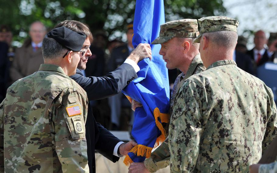 The outgoing commander of U.S. European Command, Army Gen. Curtis M. Scaparrotti, left, watches as Army Secretary Mark T. Esper passes the command's colors to incoming commander Air Force Gen. Tod. D. Wolters at Patch Barracks in Stuttgart, Germany, Thursday, May 2, 2019.