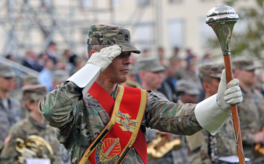 Sgt. 1st Class Andre Goncalves, the drum major for the joint U.S. Army Europe and U.S. Air Forces in Europe band at the U.S. European Command change of command ceremony salutes as distinguished visitors leave the parade field at Patch Barracks in Stuttgart, Germany, following the ceremony.