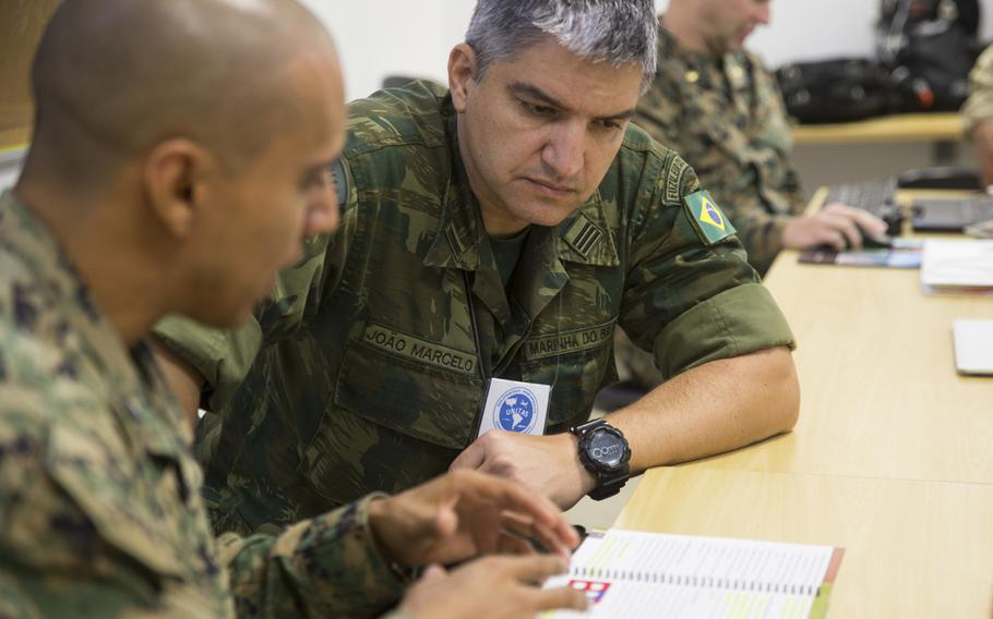 Brazilian naval infantry Lt. Col. Joao Marcelo Batista speaks with U.S. Marine Capt. Jose Negrete, the communication strategy and operations director with U.S. Marine Corps Forces, South, in Rio de Janeiro, Brazil in August 2018. President Donald Trump said he will grant special military status to Brazil, making it a ''major non-NATO ally'' in a move to boost cooperation.