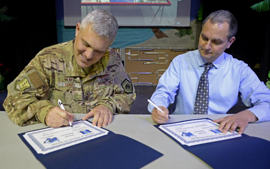 Col. Jason Terry, 435th Contingency Response Group commander, and Ramstein Middle School Principal Dan Petritz sign partnership statements during the robotics and music exhibition at Ramstein Middle School, Germany, May 9, 2019.