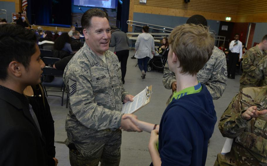 Master Sgt. Daniel Williams, 435th Contingency Response Group, congratulates Carbin Markus on his research project during the robotics and music exhibition at Ramstein Middle School, Germany, May 9, 2019.
