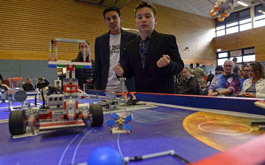 Team REV3NGERS members Alec Eschenlauer, left, and Daniel Olson look on as their autonomous robot successfully completes a mission during the robotics and music exhibition at Ramstein Middle School, Germany, May 9, 2019.