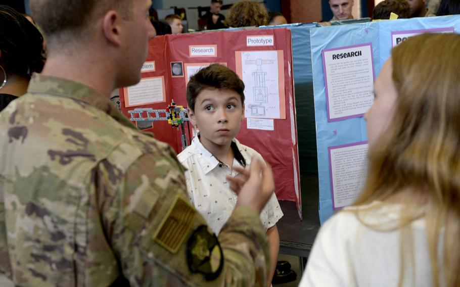 Xavian Santiago gets feedback as a 435th Contingency Response Group airman judges his team's research project during the robotics and music exhibition at Ramstein Middle School, Germany, May 9, 2019.