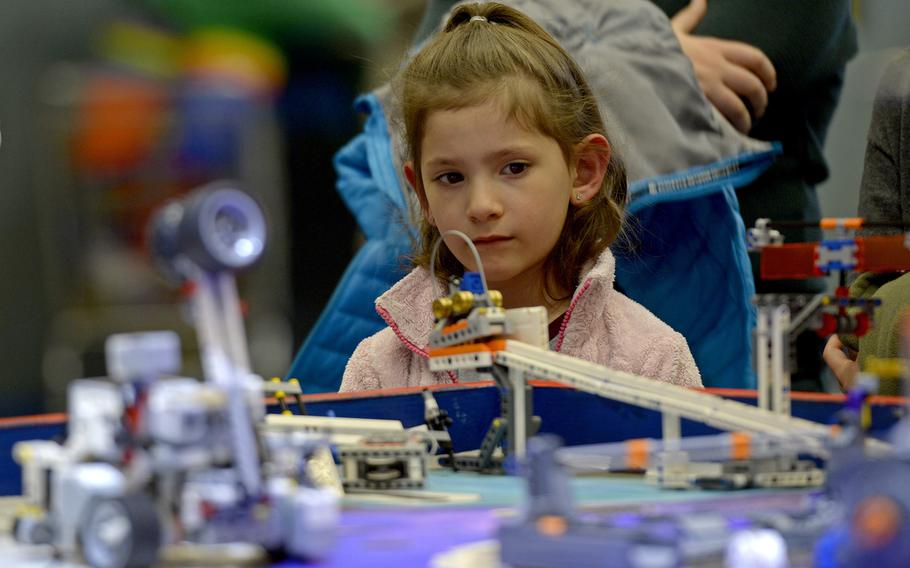 A young girl looks on as teams demonstrate their autonomous robots during the robotics and music exhibition at Ramstein Middle School, Germany, May 9, 2019.