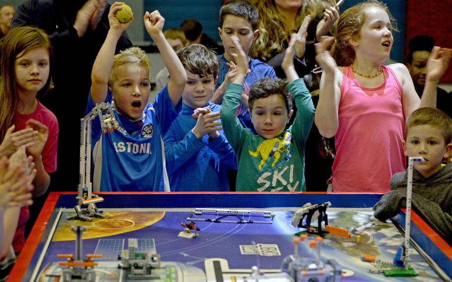 Young kids cheer as an autonomous robot completes a mission during the table demonstration at the robotics and music exhibition at Ramstein Middle School, Germany, May 9, 2019.
