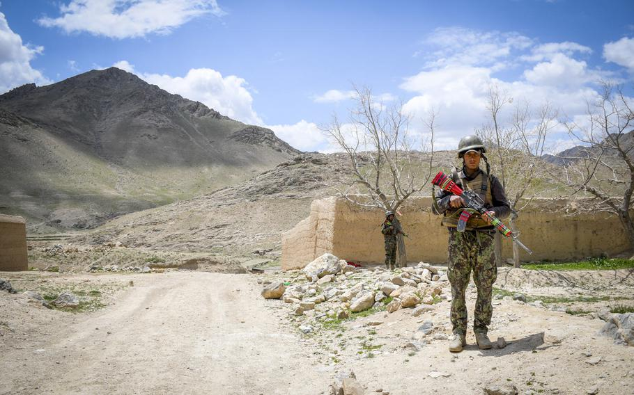 Afghan soldiers guard a temporary checkpoint in Logar province on May 2, 2019.  Taliban fighters often descend from these mountains (background) while moving around the province.