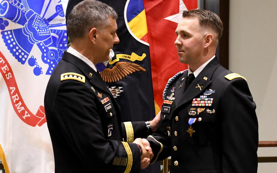 Gen. Stephen J. Townsend, commanding general of the U.S. Army Training and Doctrine Command, congratulates Maj. Nicholas Eslinger, after presenting him with the Distinguished Service Cross during an award ceremony at the Lewis and Clark Center, Fort Leavenworth, Kan., May 3, 2019.