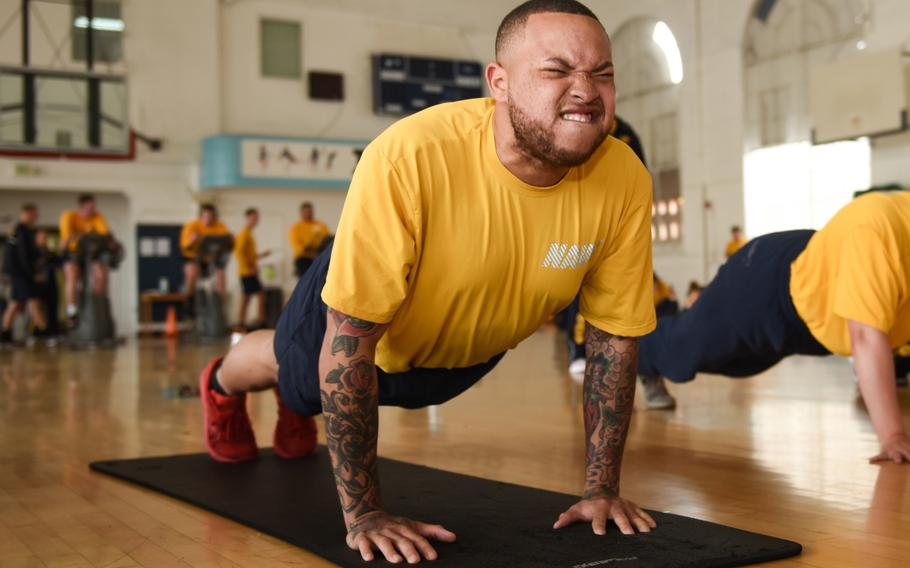 Petty Officer 2nd Class Alexander Love, assigned to the aircraft carrier USS Theodore Roosevelt, completes a pushup during the spring 2019 physical readiness test,  April 23, 2019. The Navy has issued guidelines to halt physical training of sailors who show unusual distress and let them make up the training another day.